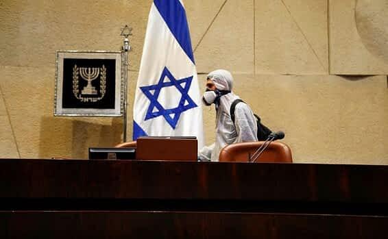 Rabotnik dezinfitsiruet zal plenarnyh zasedanij Knesseta