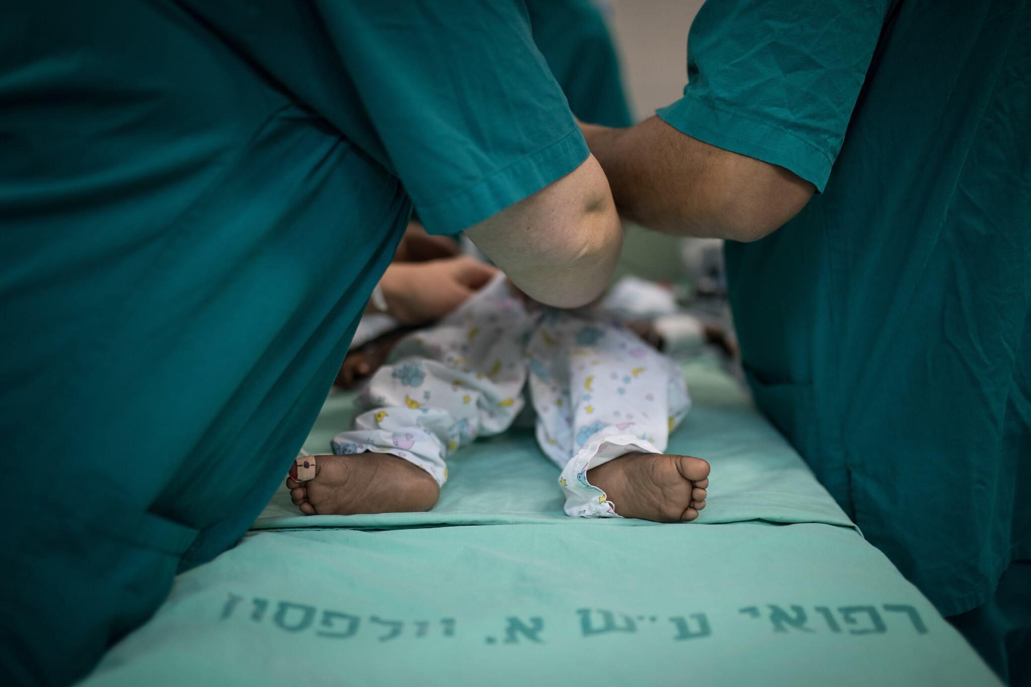 Izrailskie vrachi osmatrivayut novorozhdennogo rebenka