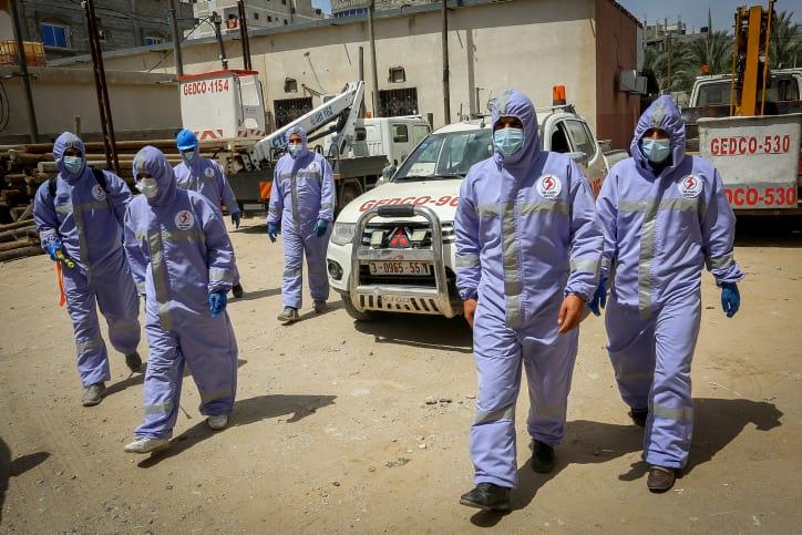 Палестинские работники проводят дезинфекцию улиц фото