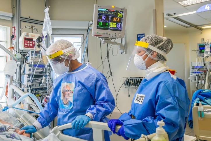Медики в костюмах индивидуальной защиты фото