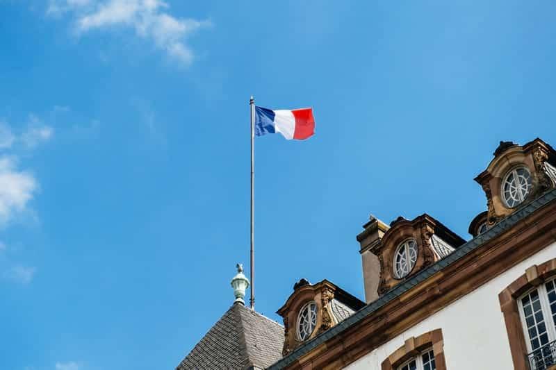 Флаг Франции на флагштоке на крыше фото