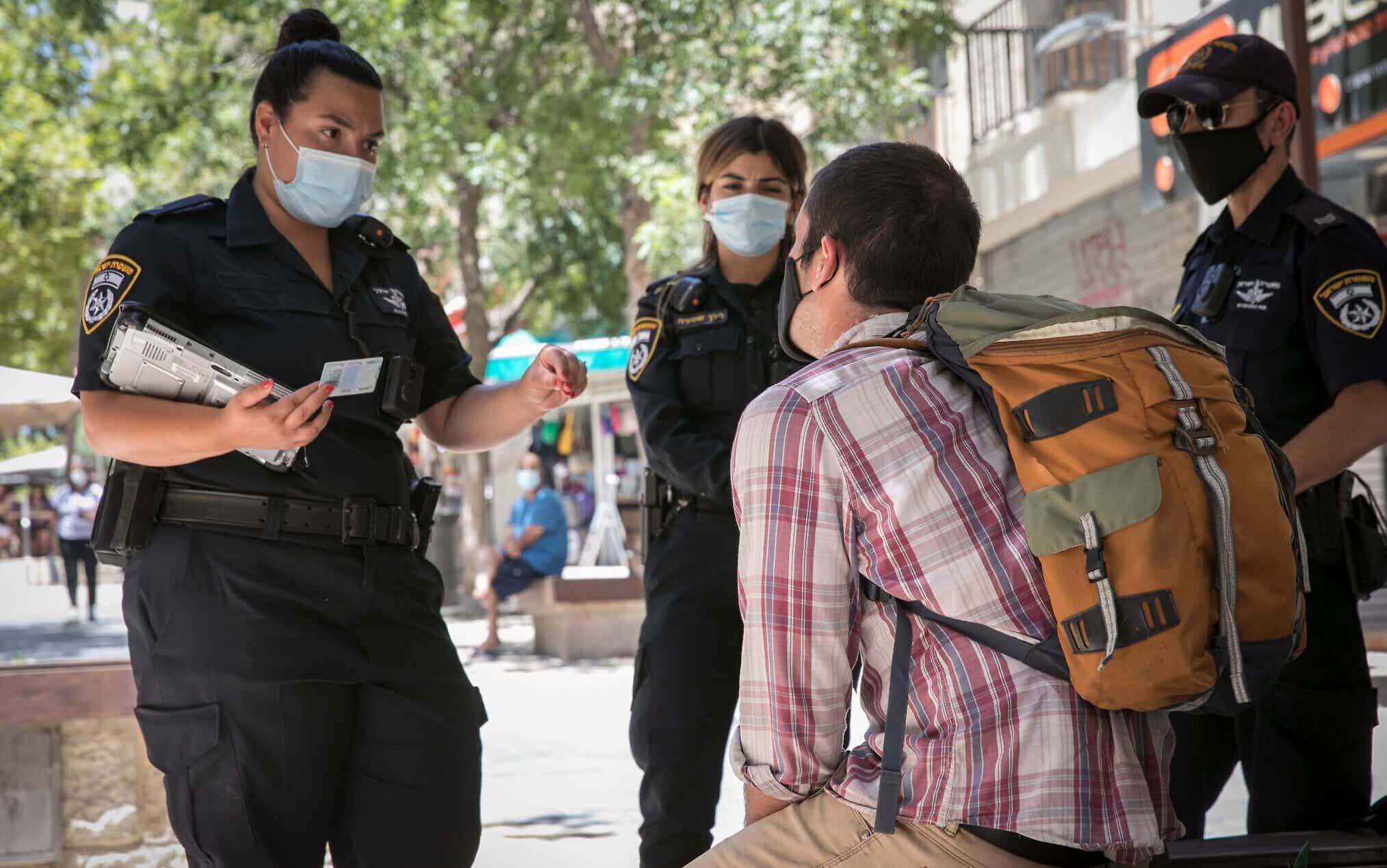 Сотрудники полиции выписывают штраф за отказ от ношения маски в Иерусалиме фото