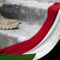 Военный рядом с флагом Судана фото